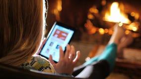 Женщина наслаждается таблеткой в уютном доме около камина задний взгляд видеоматериал