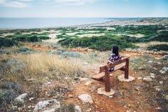 Женщина наслаждаясь видом на море сидя на стенде в красивой долине Стоковые Изображения