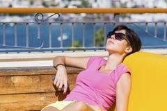 Женщина наслаждаясь летними каникулами кладя на sunbed в баре моря Стоковая Фотография
