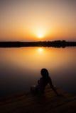 Женщина наслаждаясь заходом солнца на деревянном доке Стоковое Изображение RF
