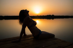 Женщина наслаждаясь заходом солнца на деревянном доке стоковые изображения