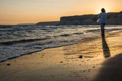 женщина наслаждаясь заходом солнца на пляже Стоковые Фотографии RF