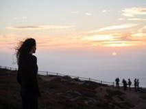 Женщина наслаждаясь заходом солнца Стоковые Изображения RF