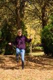 Женщина наслаждаясь листьями падения стоковое изображение