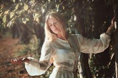 Женщина наслаждаясь мягким светом захода солнца стоковая фотография