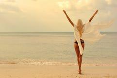 Женщина наслаждаясь свободой на пляже на заходе солнца Стоковое Изображение RF