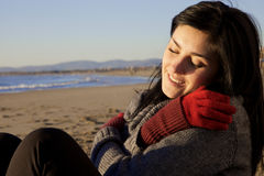 Женщина наслаждаясь солнцем на пляже в холодном зимнем дне стоковое фото