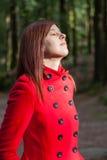Женщина наслаждаясь теплом солнечного света зимы на лесе стоковые изображения rf