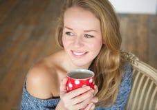 Женщина наслаждаясь чашкой чаю дома Стоковая Фотография RF