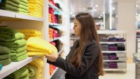 Женщина находя новые полотенца в магазине супермаркета магазина сток-видео