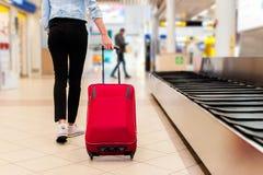 Женщина на авиапорте, нося ее сумку вагонетки Стоковое Изображение