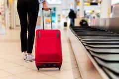 Женщина на авиапорте, нося ее сумку вагонетки Стоковые Фото