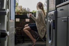 Женщина на балконе выпивая кофе Стоковые Изображения