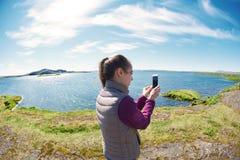 Женщина на береге озера Thingvallavatn tne в национальном парке Thingvellir Стоковая Фотография