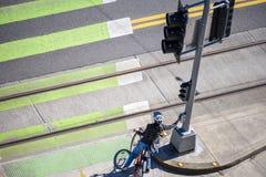 Женщина на велосипеде подготавливает пересечь дорогу на пешеходный переход стоковая фотография