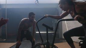 Женщина на велотренажере на спортзале с тренерами сток-видео