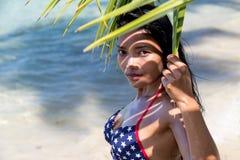 Женщина на взглядах украдкой пляжа от зеленых лист ладони Стоковое Изображение RF