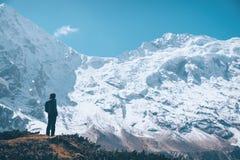 Женщина на горной тропе и смотреть на снеге покрыли утесы Стоковые Изображения