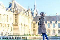 Женщина на дворце Chantilly Молодая туристская девушка восхищая взгляды Предпосылки bokeh портрета мягкие стоковая фотография