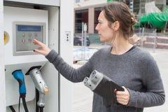 Женщина на зарядной станции электрического автомобиля стоковые фотографии rf