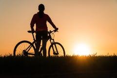 Женщина на заходе солнца от велосипеда велосипеда захода солнца спорт женщины практикуя стоковое фото