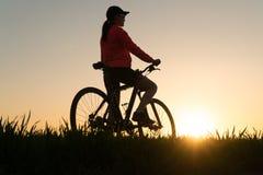 Женщина на заходе солнца от велосипеда велосипеда захода солнца спорт женщины практикуя стоковая фотография rf