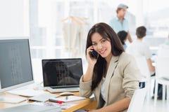 Женщина на звонке на столе с коллегами позади в офисе Стоковое Изображение RF