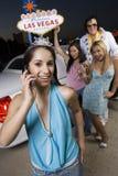 Женщина на звонке с друзьями и имитатором Elvis Presley на заднем плане стоковые изображения