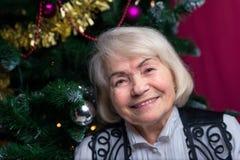 Женщина на зрелом времени против рождественской елки Стоковое фото RF