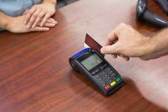 Женщина на кассовом аппарате оплачивая с кредитной карточкой Стоковые Фото