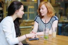 Женщина 2 на кафе outdoors Стоковые Изображения
