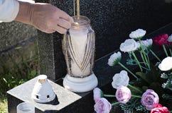 Женщина на кладбище освещает свечу со спичкой на могиле стоковое изображение