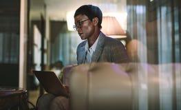 Женщина на командировке используя ноутбук в лобби гостиницы стоковая фотография rf