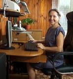 Женщина на компьютере на дому стоковые фото