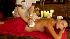 Женщина на красном полотенце имеет горячий массаж poultice в салоне 4k курорта