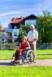 Женщина на кресло-коляске и более старом человеке Стоковые Изображения