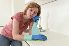 Женщина на кухне при резиновая моя утомлянная ткань перчаток и чистка тензида пробуренная и Стоковая Фотография RF
