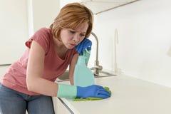 Женщина на кухне при резиновая моя утомлянная ткань перчаток и чистка тензида пробуренная и Стоковое Изображение