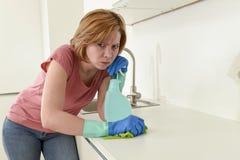 Женщина на кухне при резиновая моя утомлянная ткань перчаток и чистка тензида пробуренная и Стоковые Изображения