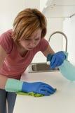 Женщина на кухне при резиновая моя утомлянная ткань перчаток и чистка тензида пробуренная и Стоковое фото RF