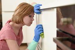 Женщина на кухне при резиновая моя утомлянная ткань перчаток и чистка тензида пробуренная и Стоковые Изображения RF