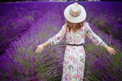 Женщина на ликовании поля лаванды в соломенной шляпе стоковая фотография rf