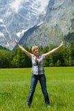 женщина на луге с горами на заднем плане показывает утеху стоковые фотографии rf