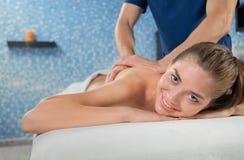 Женщина на массаже лежа на кресле и смотря камеру во спа стоковая фотография