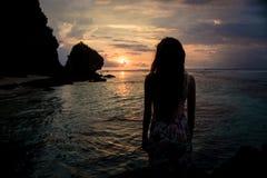 Женщина на море наслаждаясь заходом солнца на Бали Стоковые Фотографии RF