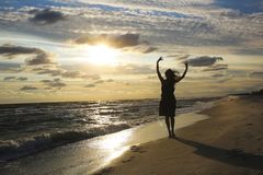 Женщина на морском побережье на заходе солнца стоковое фото