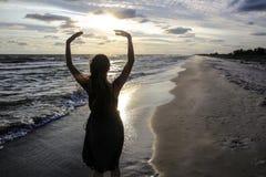 Женщина на морском побережье на заходе солнца стоковые фотографии rf