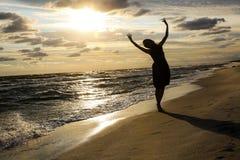 Женщина на морском побережье на заходе солнца стоковые изображения