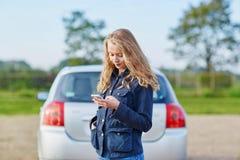 Женщина на дороге около сломленного автомобиля вызывая для помощи Стоковая Фотография
