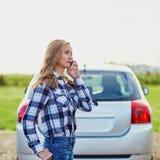 Женщина на дороге около сломленного автомобиля вызывая для помощи Стоковые Изображения